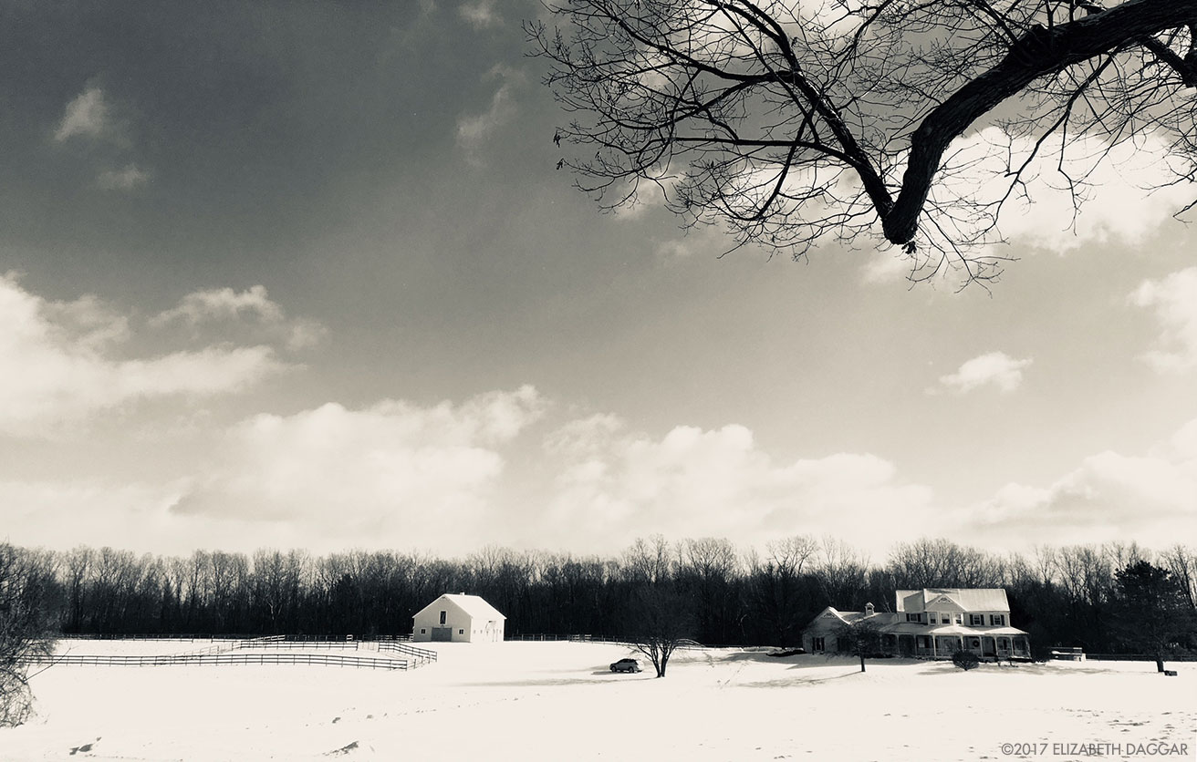 black and white photograph of a farm house in a snowy field