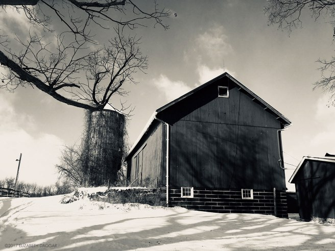 black and white photograph of a barn an silo on a snowy hill
