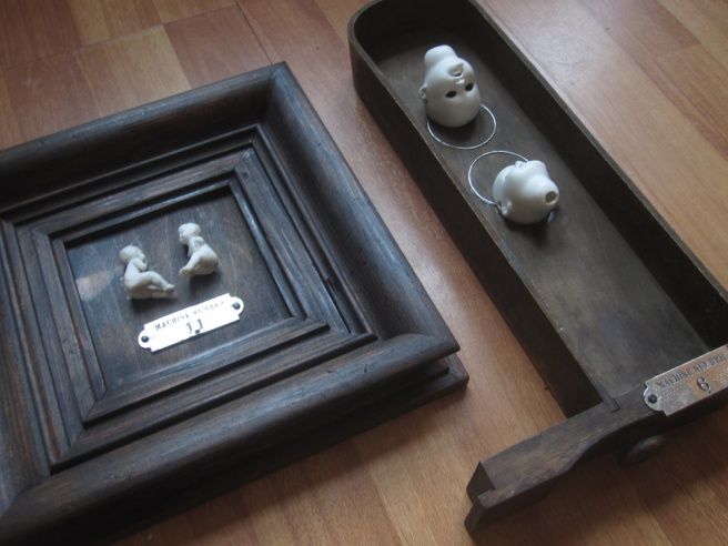 two assemblages, with porcelain dolls and metal bits