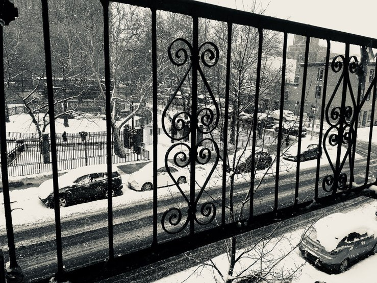 looking out on a snowy street through a fire escape (photo)