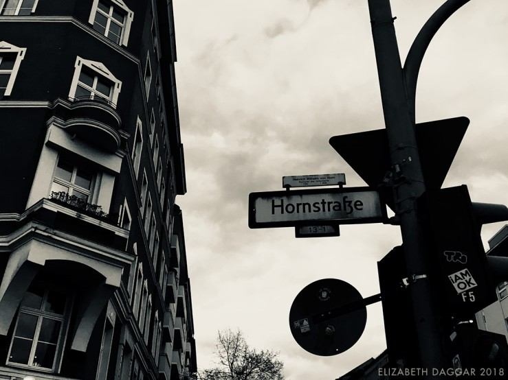 b&w photo of a corner building and street signs in Berlin