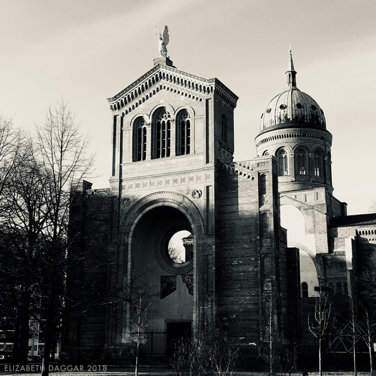 B&W photo of the exterior structure of a stone cathedral whose interior is empty in a park in Berlin