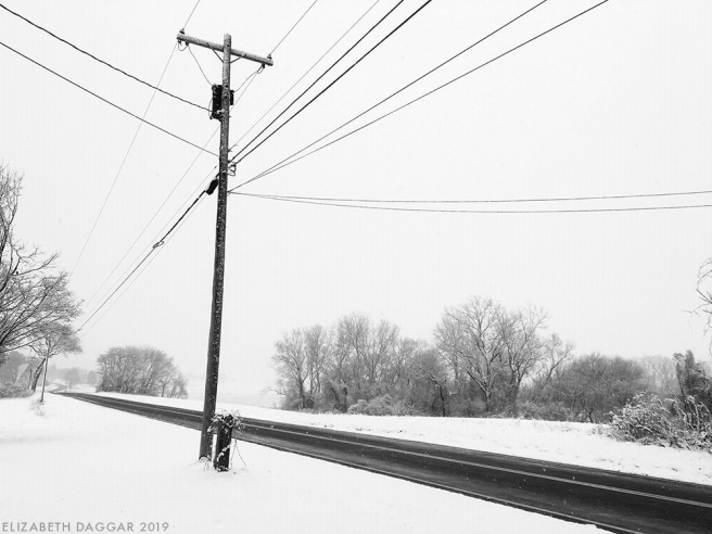 telephone pole and wires in snow (b&w photo)
