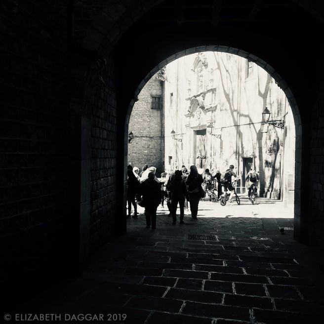 silhouettes of backlit people walking through a shadowed archway