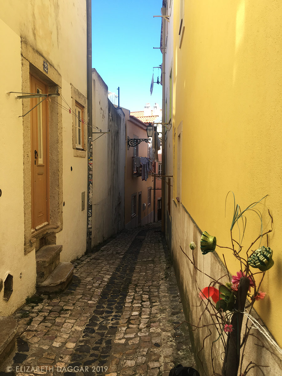 an inviting alleyway of yellow in Alfama, Lisbon