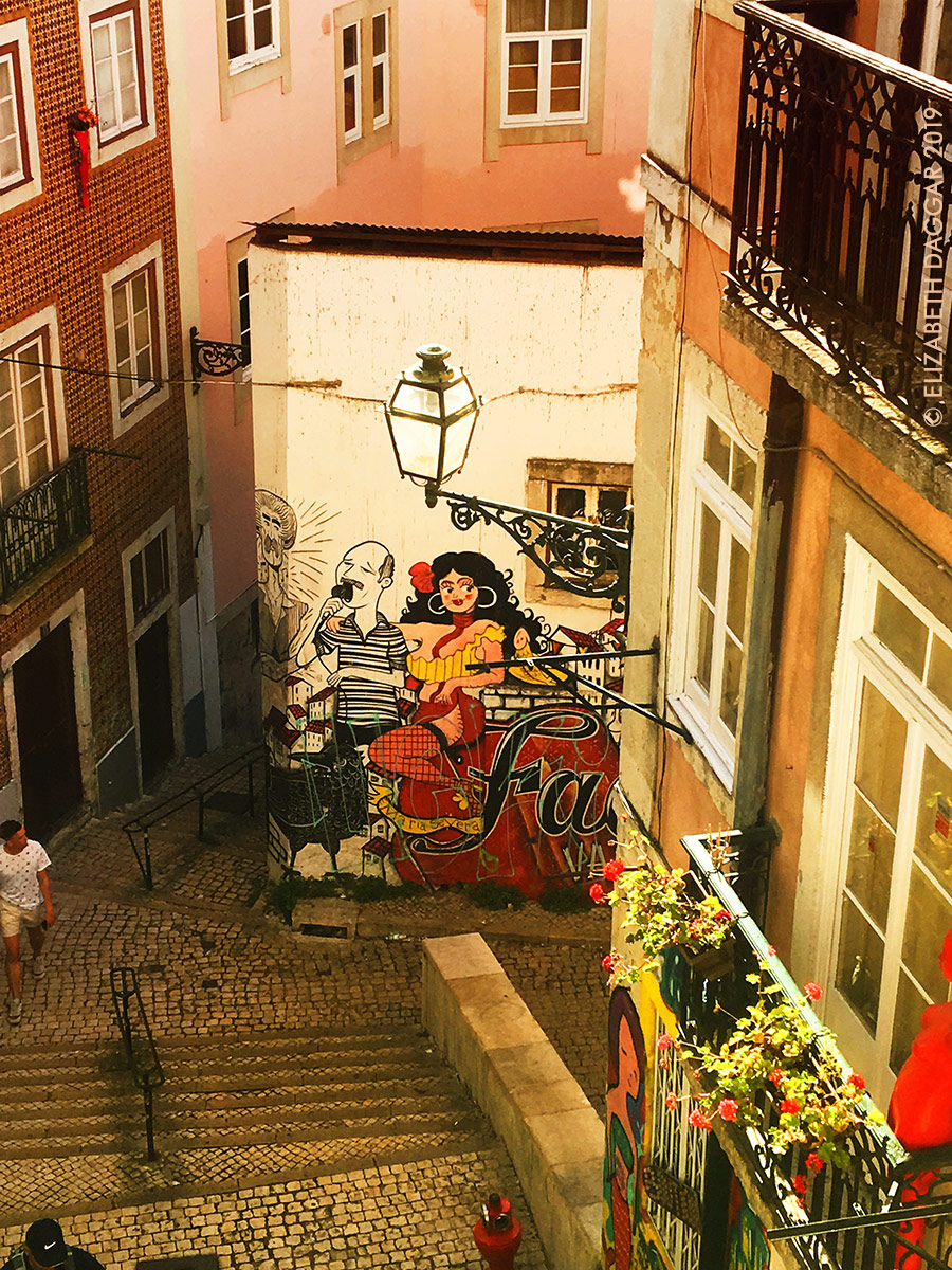 Looking down steps into a courtyard with a mural devoted to Fado